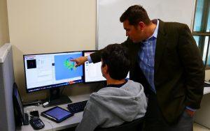 Reuben Kraft observing a brain model with a graduate student
