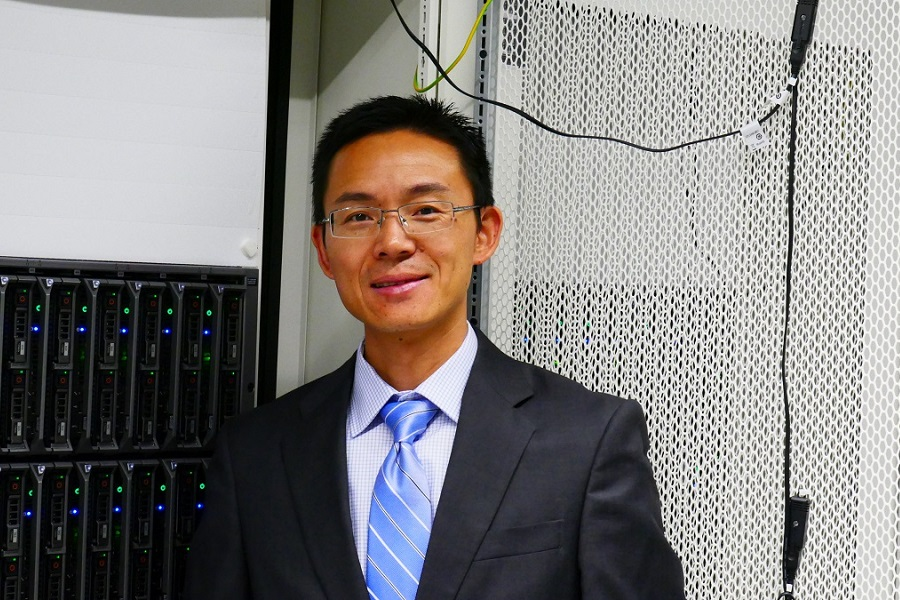 Xiaofeng Liu in front of computational hardware