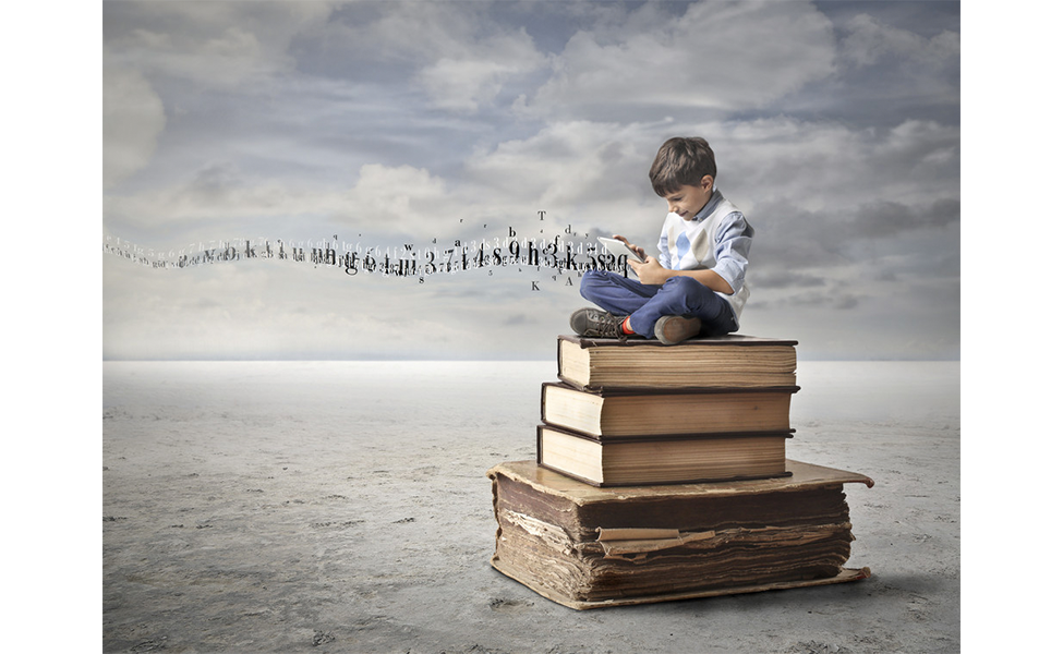 Boy sits on stack of books using tablet