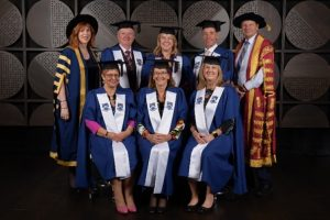 fellowship winners pose in traditional academic robes